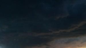 Schwarze Gewitterwolken mit Silberstreif am Horizont